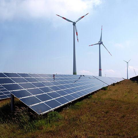 Windpark Schneebergerhof. Im Vordergrund eine Photovoltaikanlage mit Dünnschichtsolarzellen. In der Bildmitte eine Windturbine vom Typ Enercon E-66 (1,5 MW), rechts daneben eine Enercon E-126 (7,5 MW) und ganz rechts wieder eine Enercon E-66.